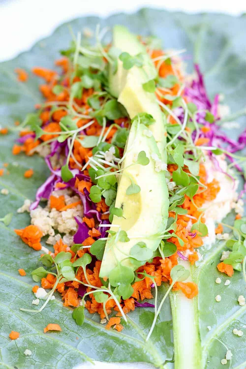 Collard leaf face up with veggies and avocado on top.