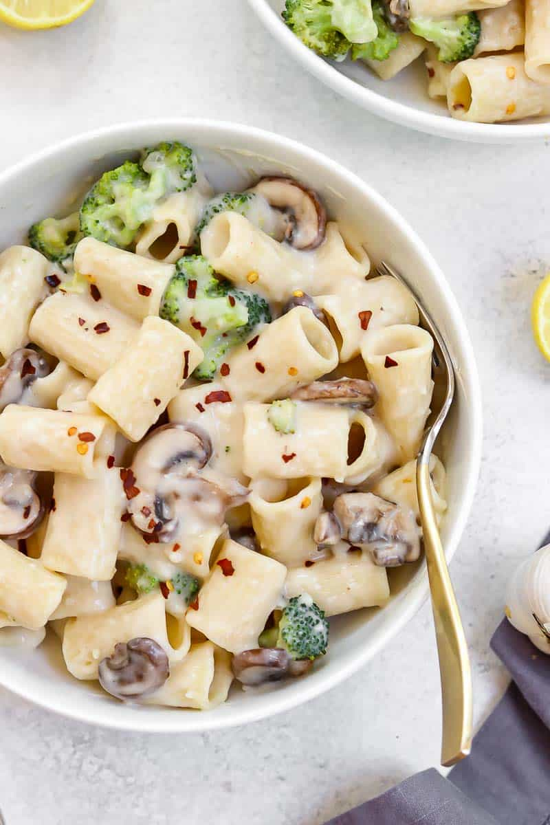 Mushroom rigatoni in a white bowl with a gold fork.