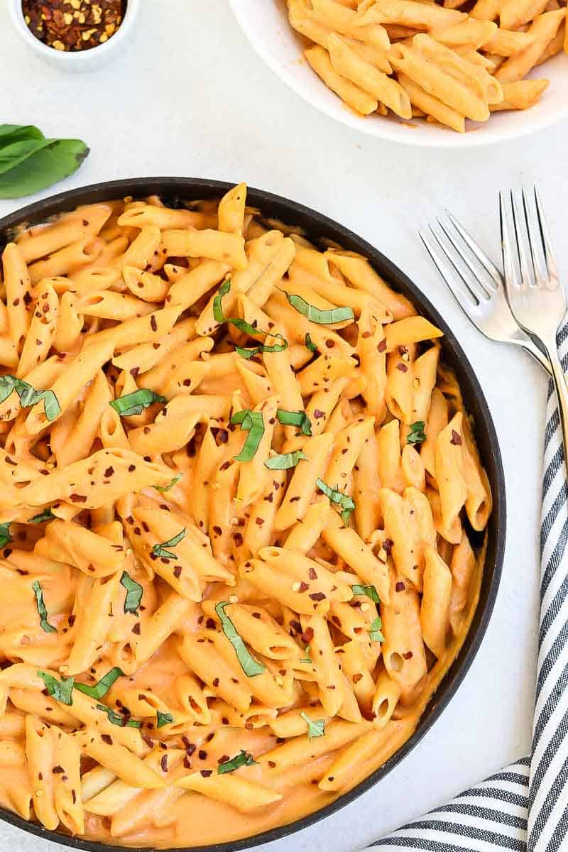 Roasted red pepper pasta in a skillet with fresh basil and red pepper flakes on top.