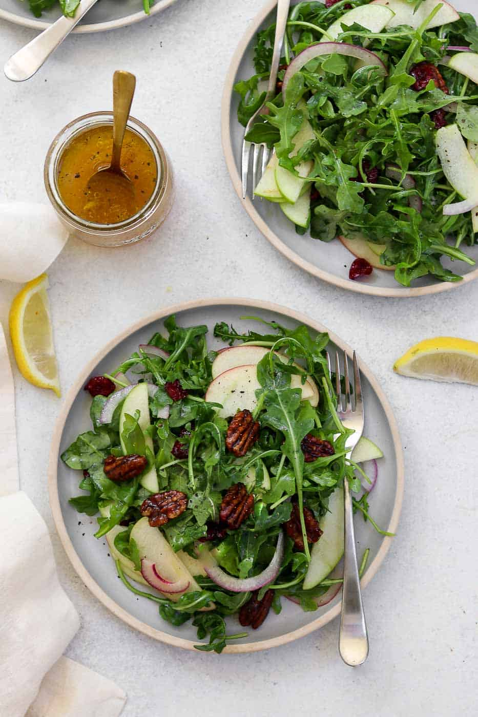 Two plates with apple arugula salad and lemon wedges.