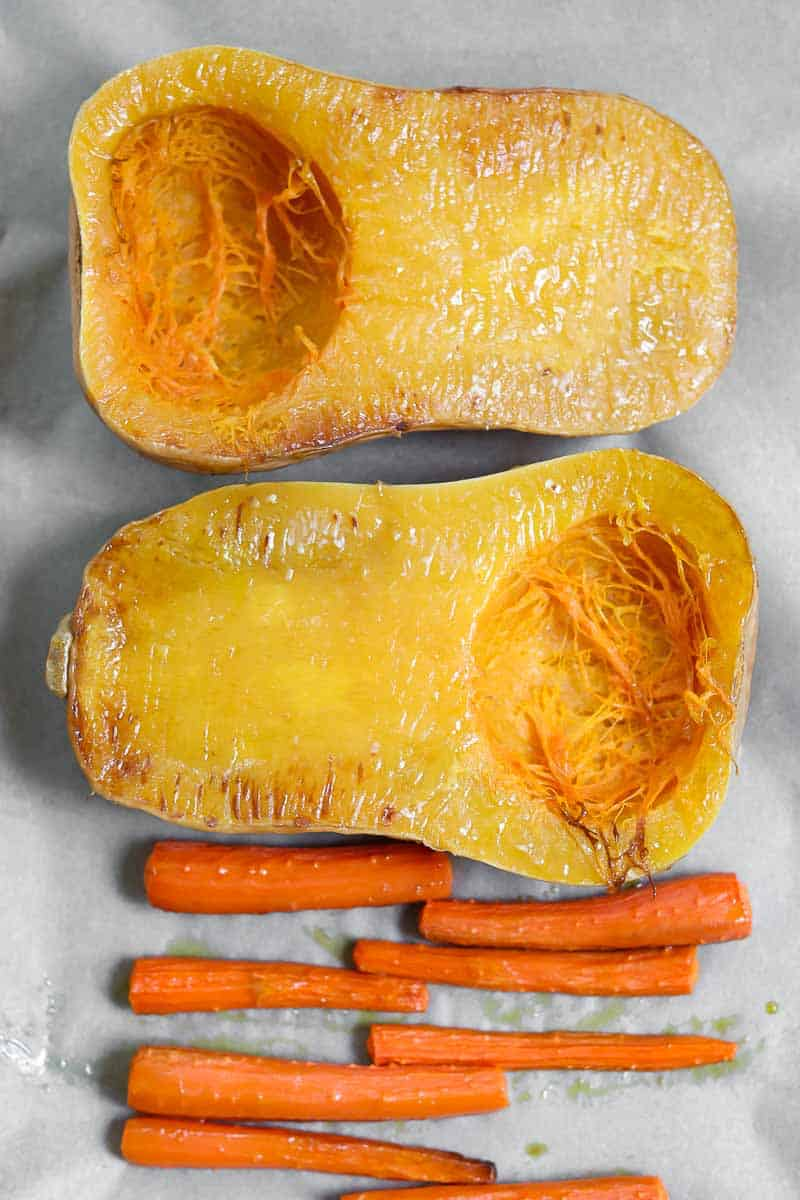2 halves of butternut squash and carrots on a baking tray.