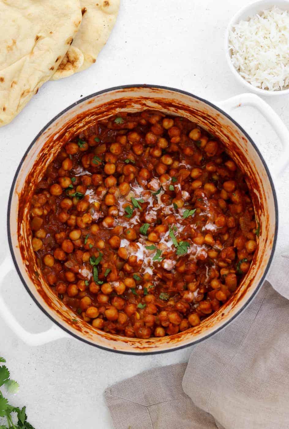 Final chana masala in a white pot.
