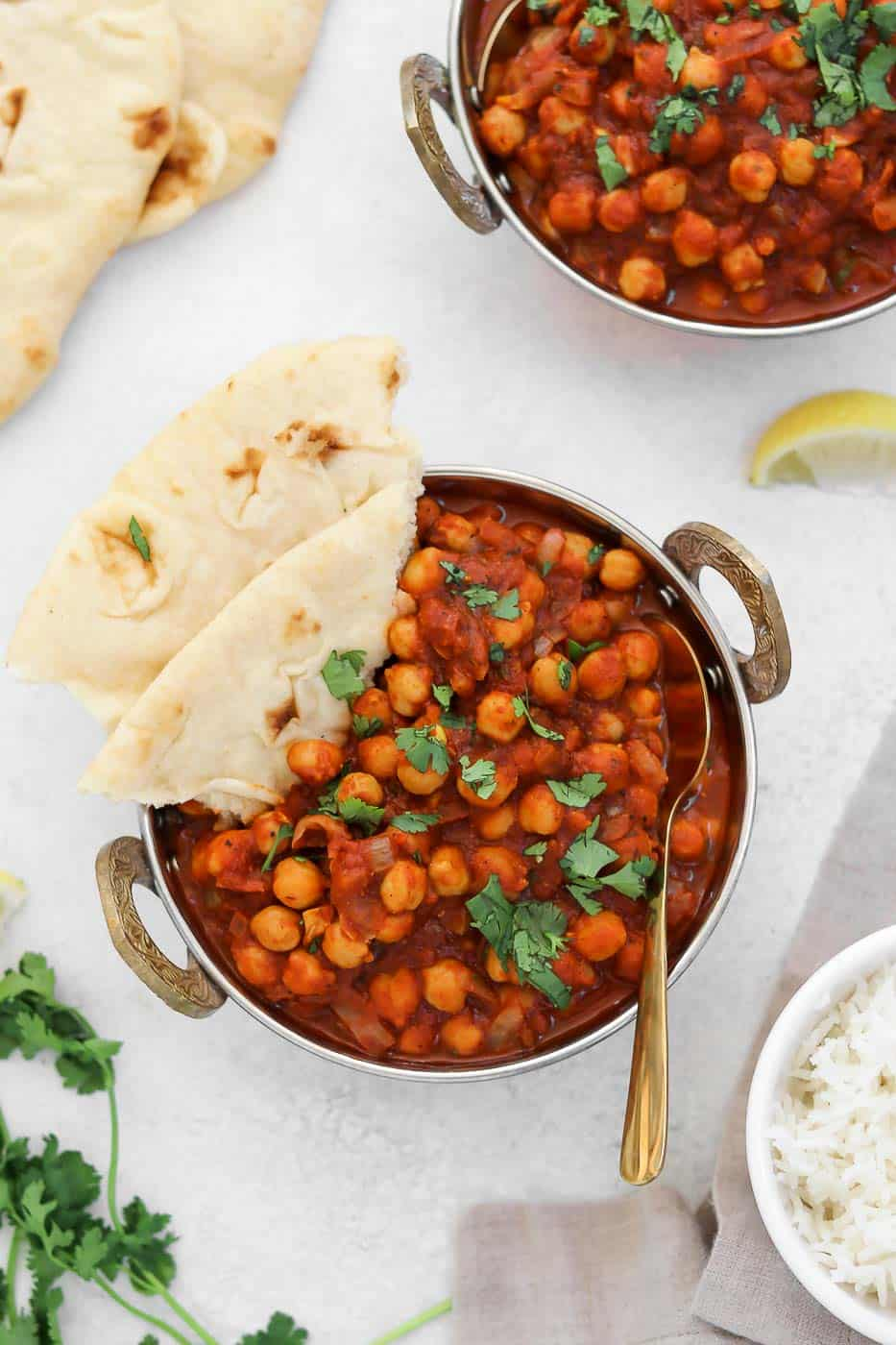 Chana masala in a gold dish with naan on the side.