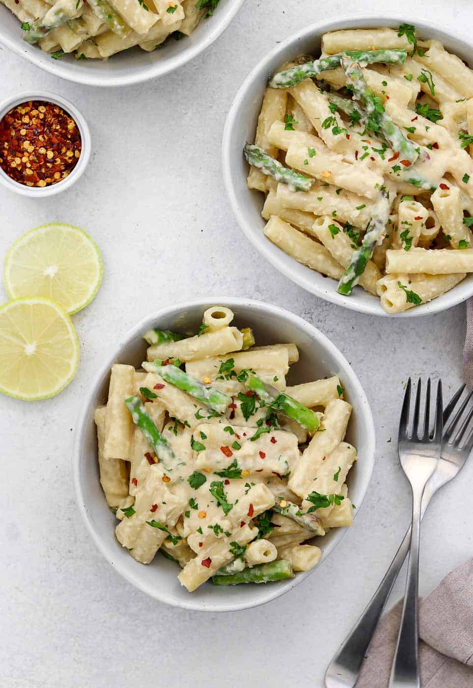 Three bowls of pasta with lemon and red pepper flakes.