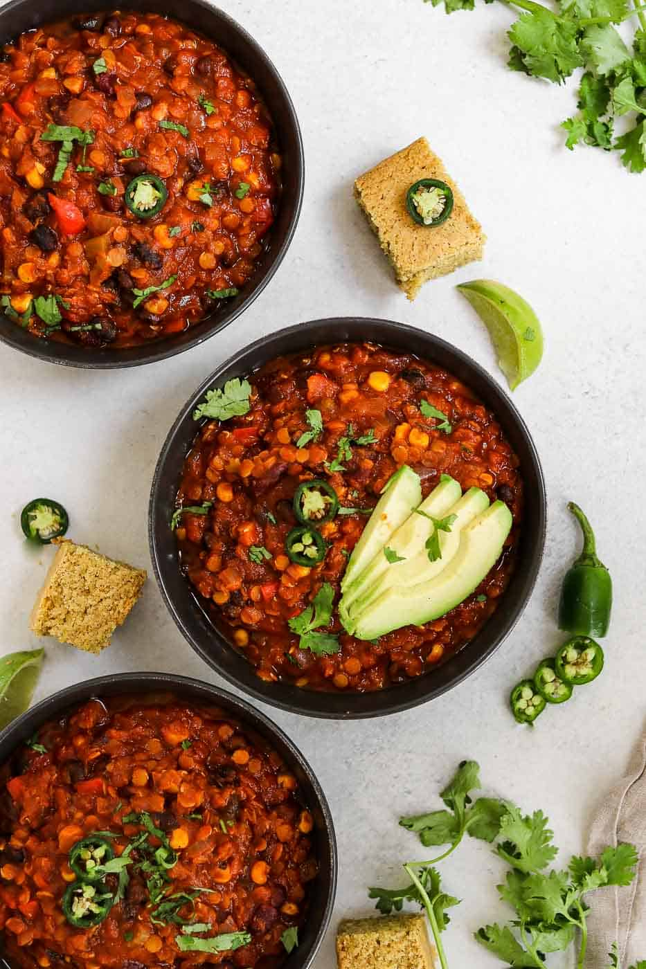 Three bowls of chili with cornbread, cilantro and avocado.