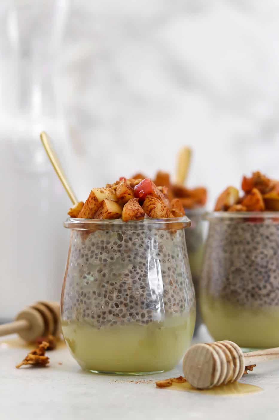 Overnight chia pudding with apples on top and a gold spoon.