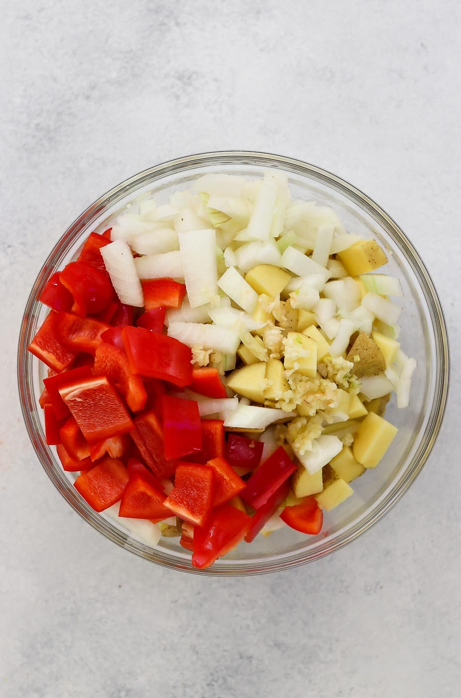 Chopped peppers, onion and potatoes in a bowl,