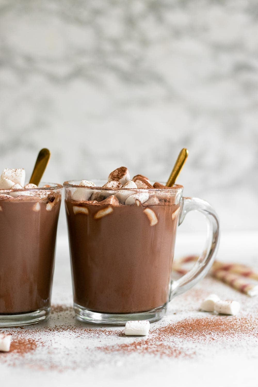 Healthy hot chocolate in a glass mug with a gold spoon on the side.