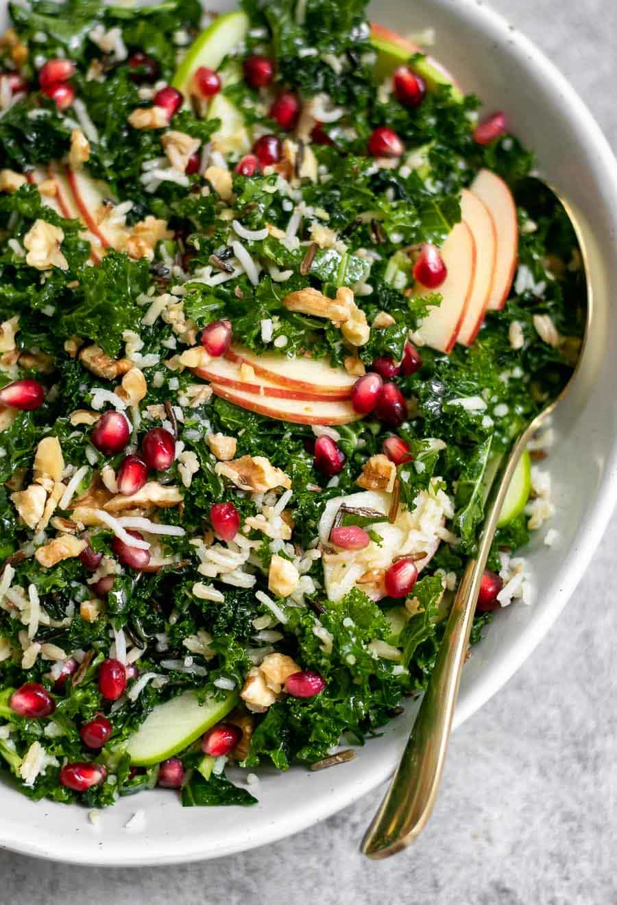 Kale apple salad with a gold spoon on the side.