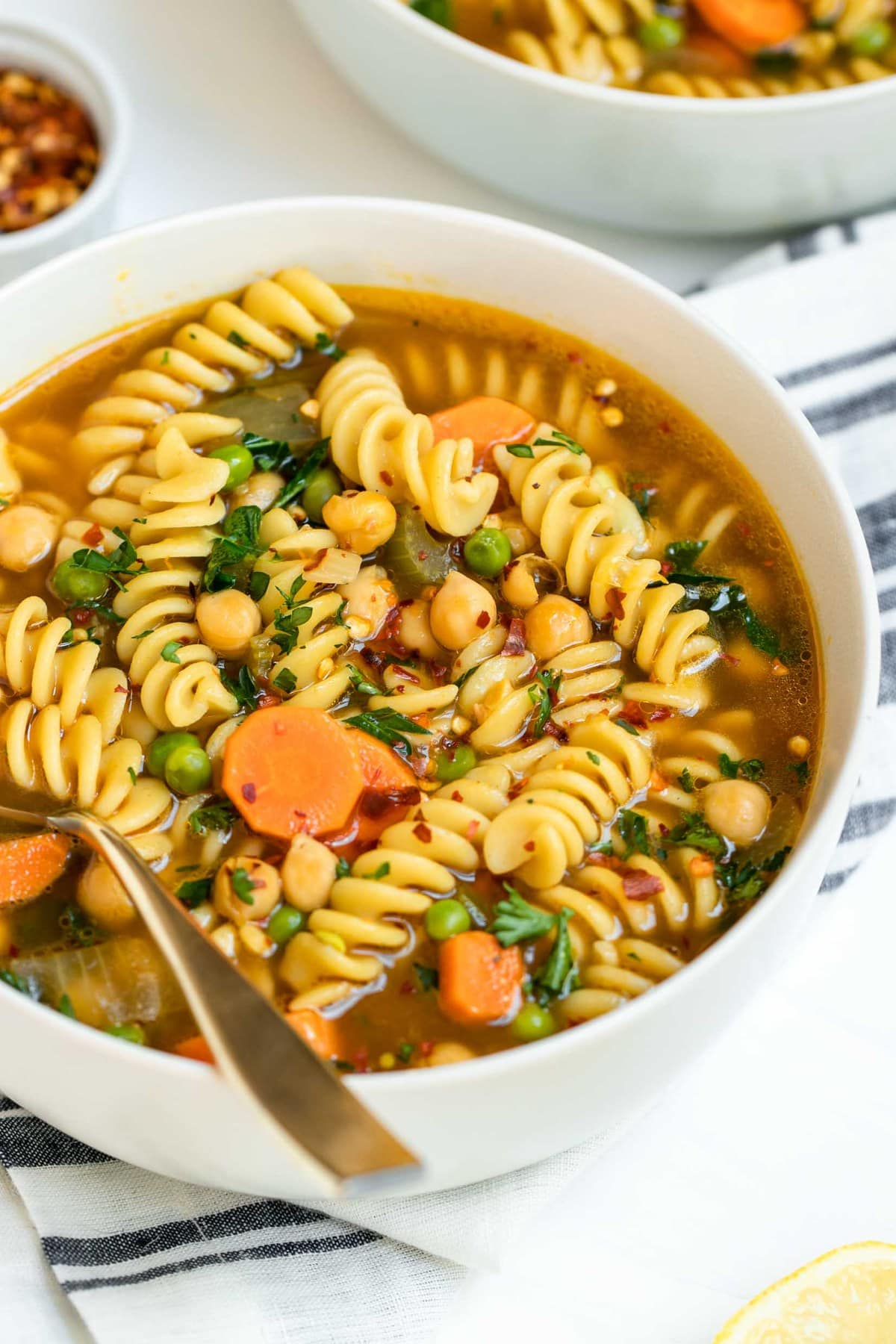 Chickpea noodle soup in a small white bowl.