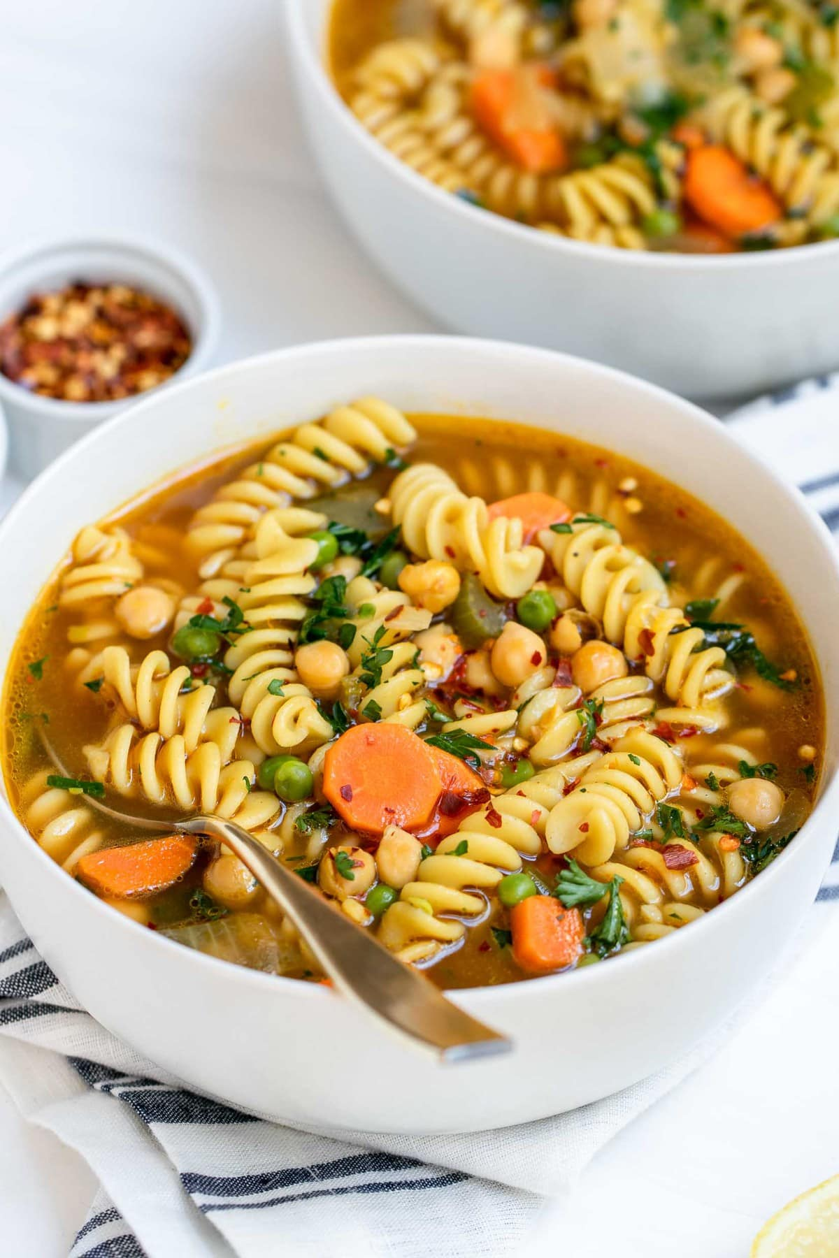 Vegetarian chickpea noodle soup with vegetables in a white bowl.