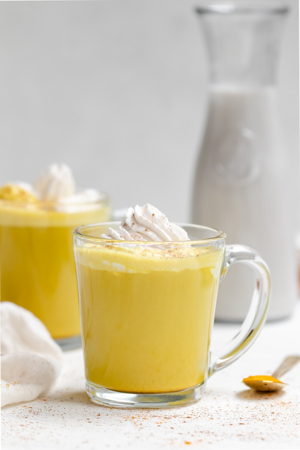 Golden milk latte recipe in a glass cup with whipped cream.