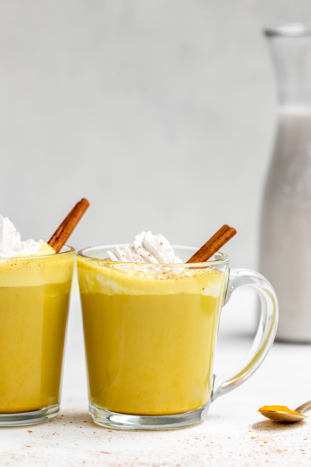 Golden milk latte with cinnamon sticks in glass mugs.