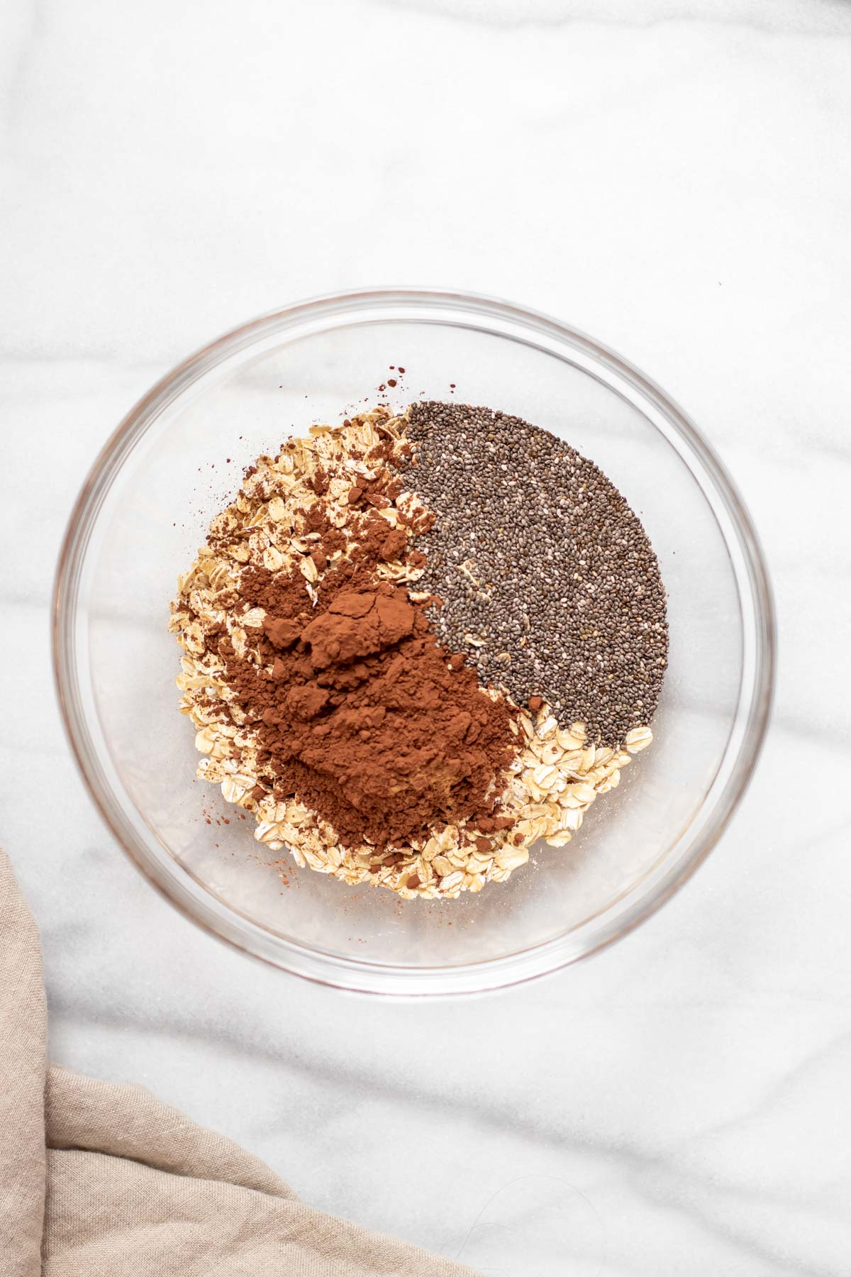 Oats, chia seeds and cocoa in a glass bowl.