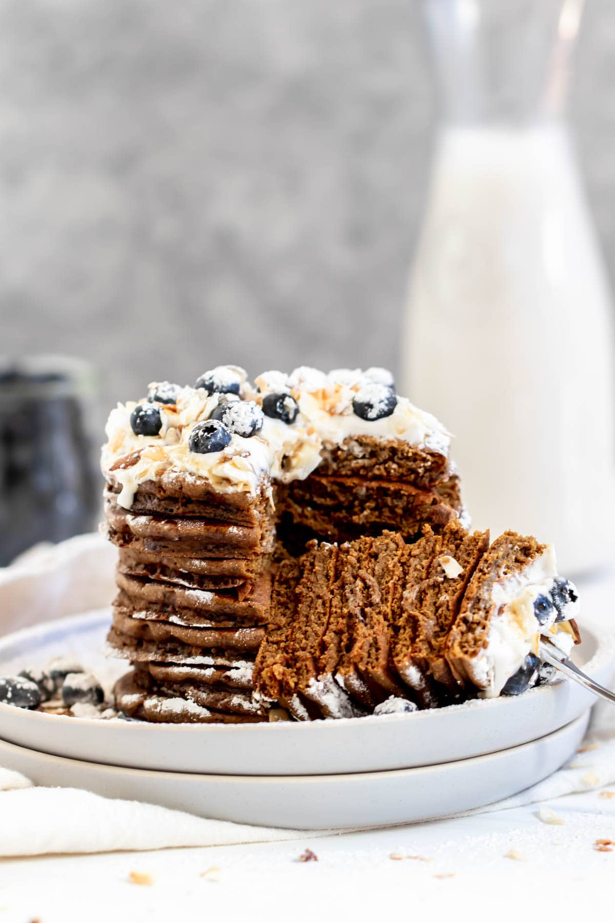 Stack of gingerbread pancakes with a fork on the side pulling out a bite.