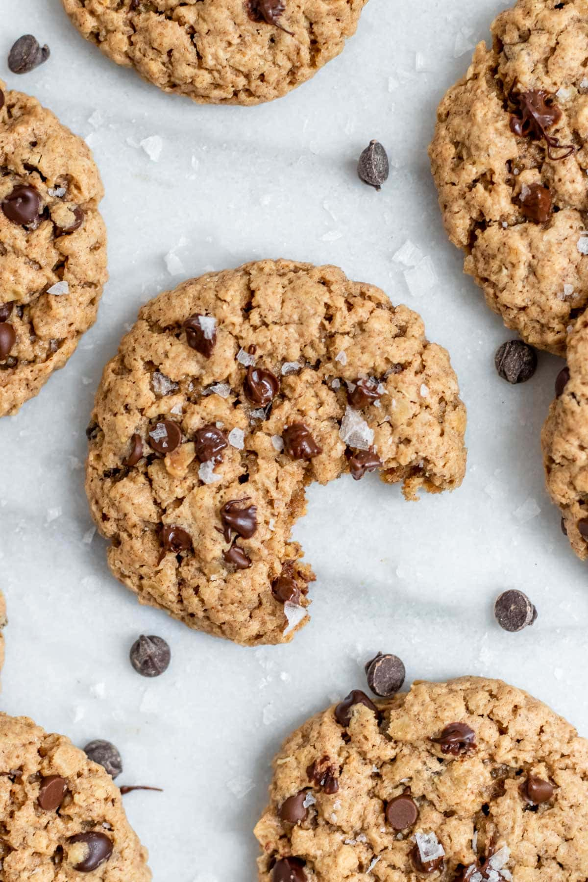 vegan oatmeal chocolate chip cookies on a marble backdrop with a bite taken out.
