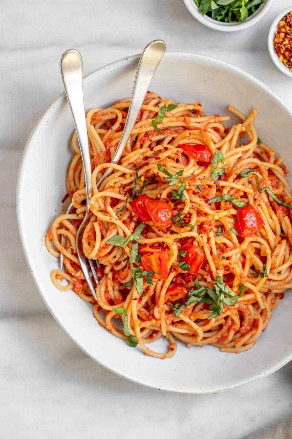 Vegan spaghetti sauce with pasta in a large bowl with two forks.