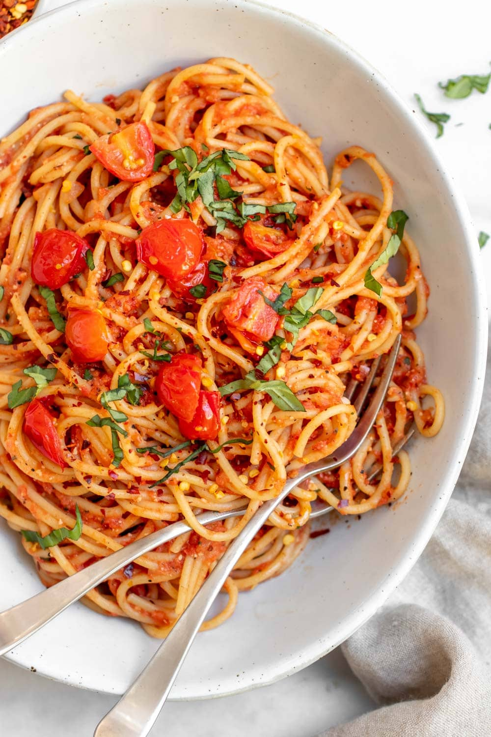 Up close of pasta pomodoro with fresh basil on top.