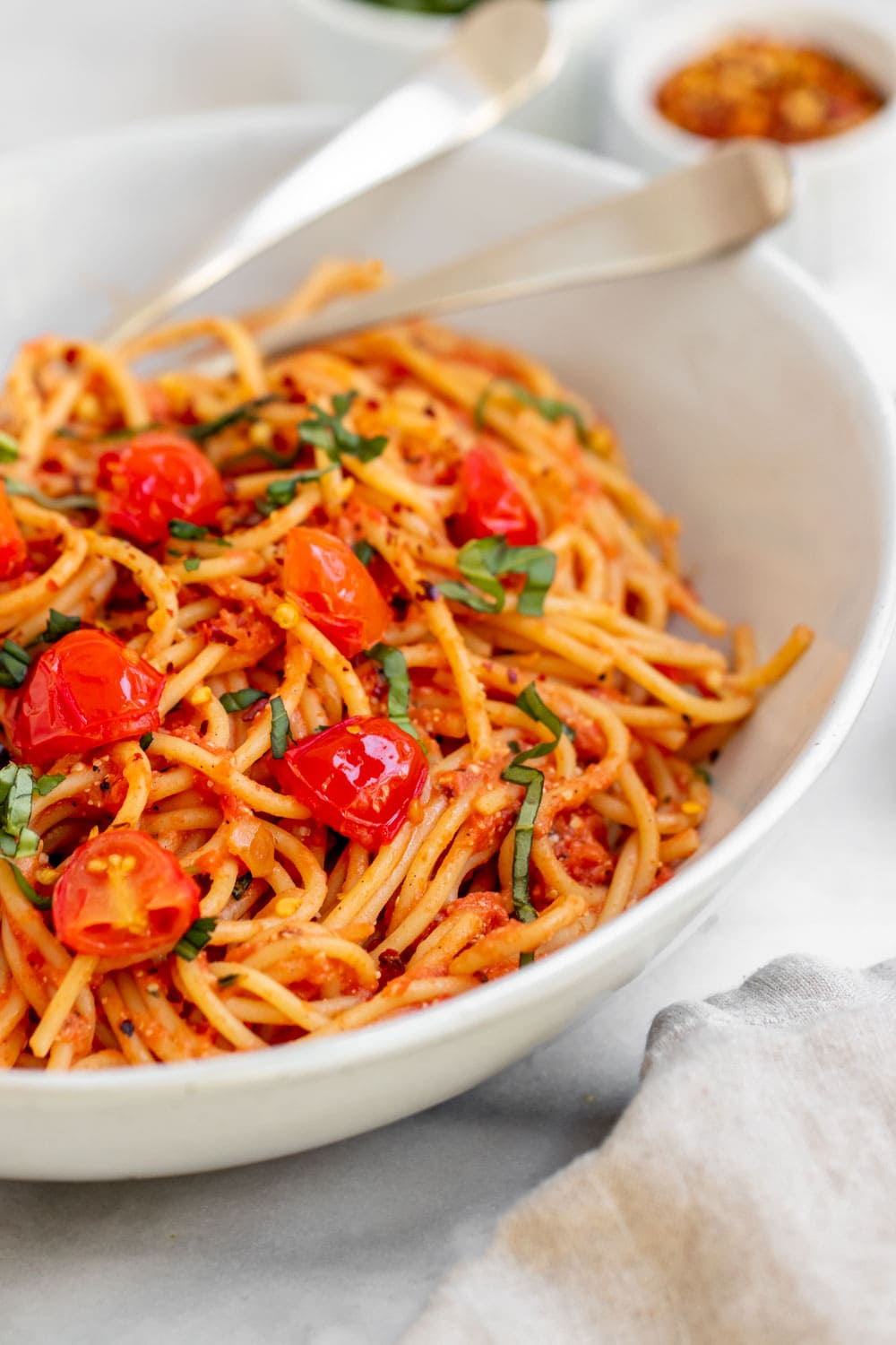 Angled view of pasta pomodoro with fresh tomatoes on top.
