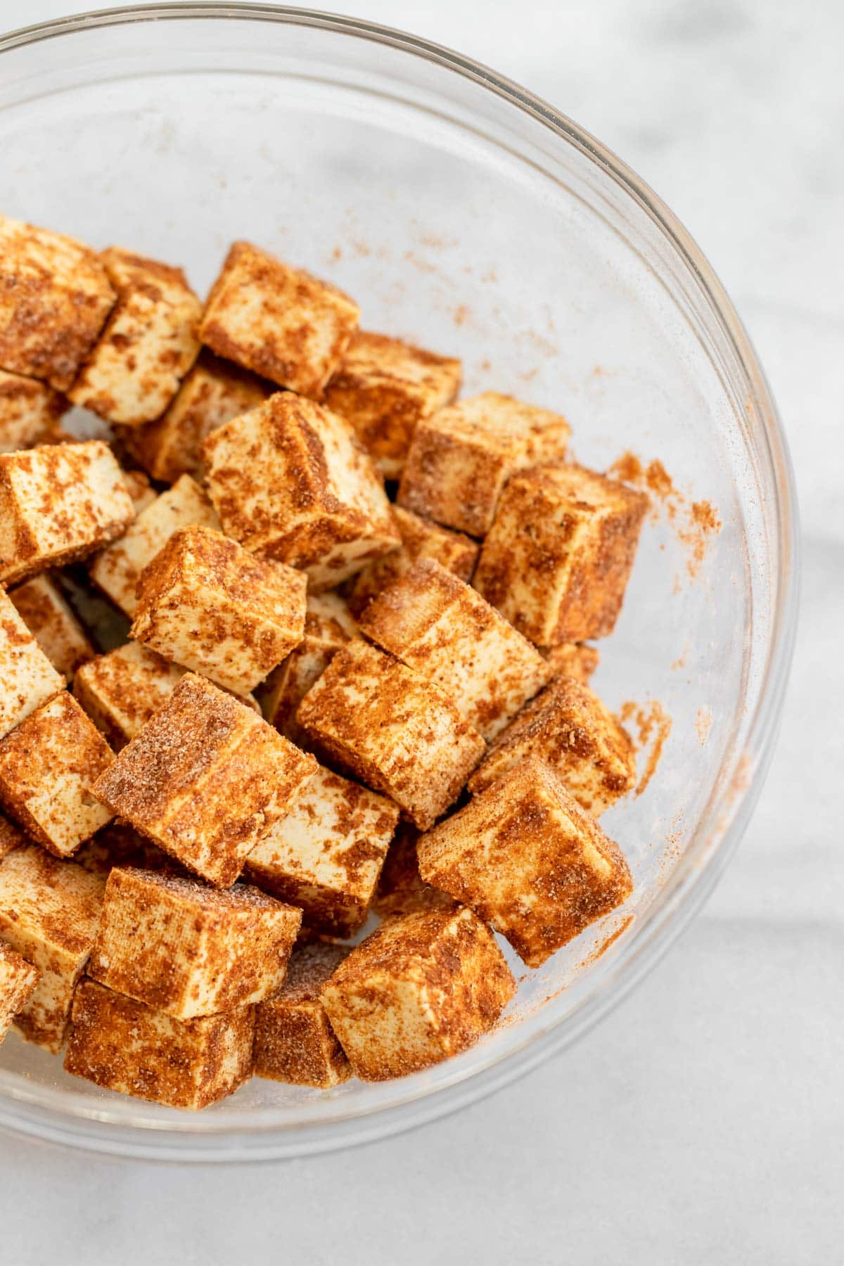 Tofu with seasonings in a glass bowl.