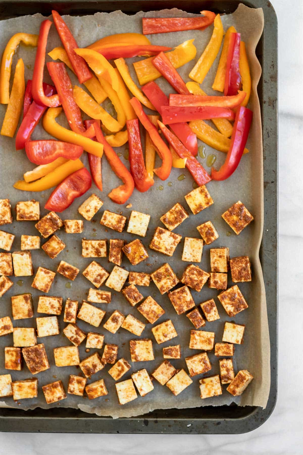 Tofu and peppers on a baking pan before going in the oven.