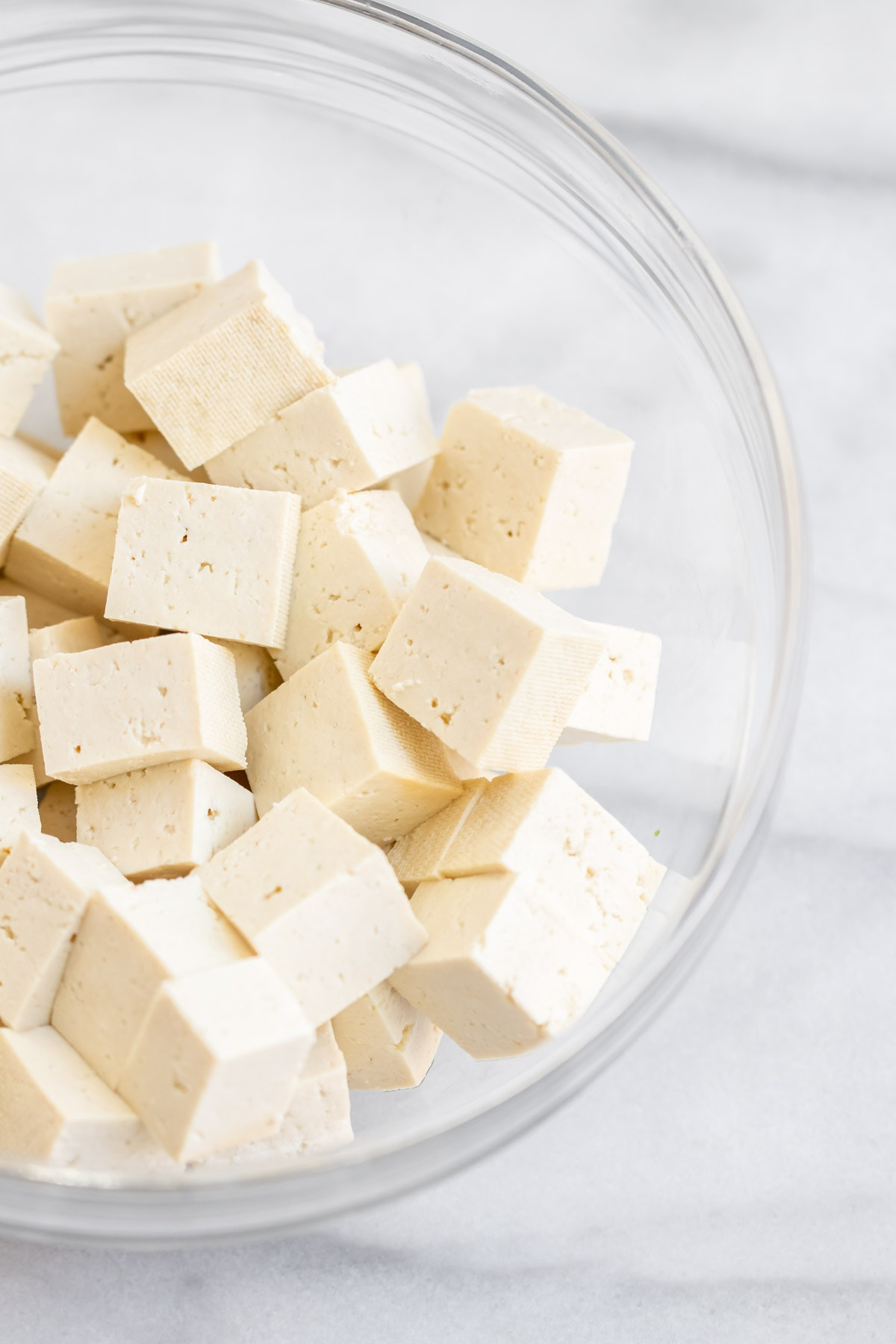 Cubed tofu in a glass bowl.