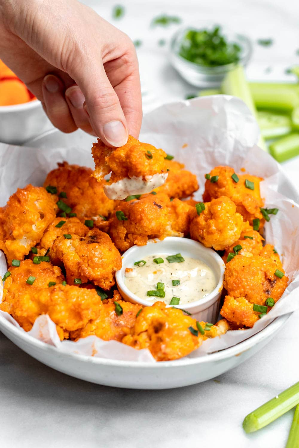 Dipping the vegan buffalo cauliflower in the ranch dipping sauce.