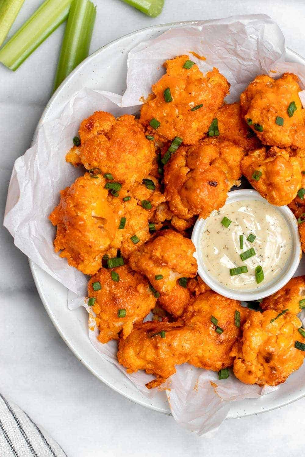 Baked buffalo cauliflower with chives on top in a large bowl.
