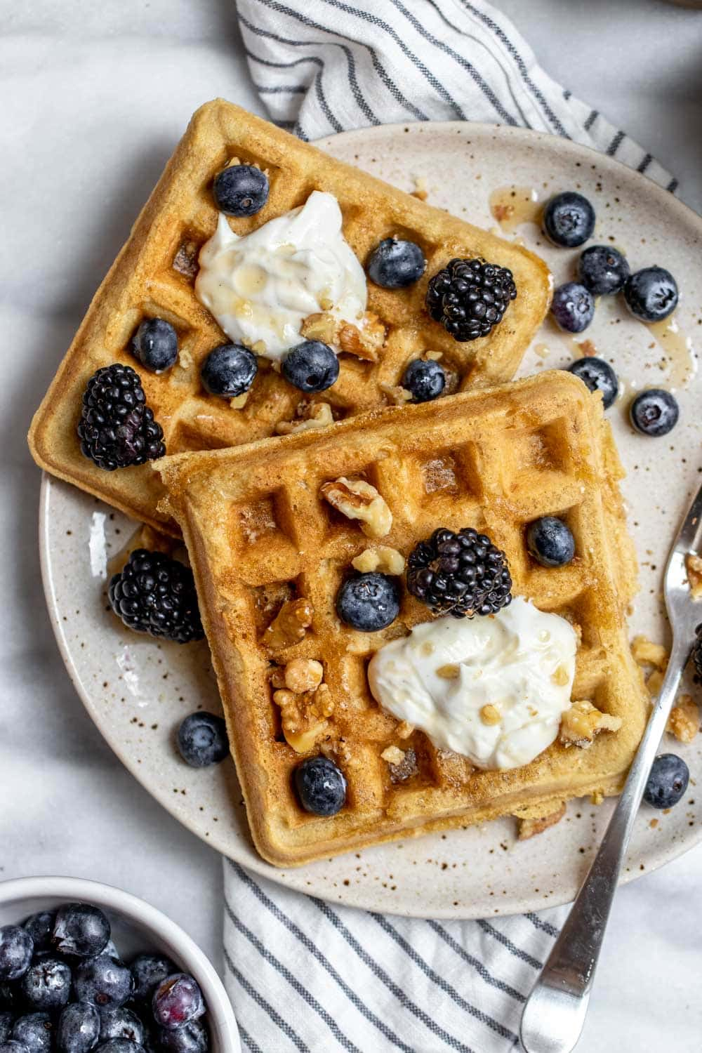 Two almond flour waffles on a plate with yogurt and berries on top.