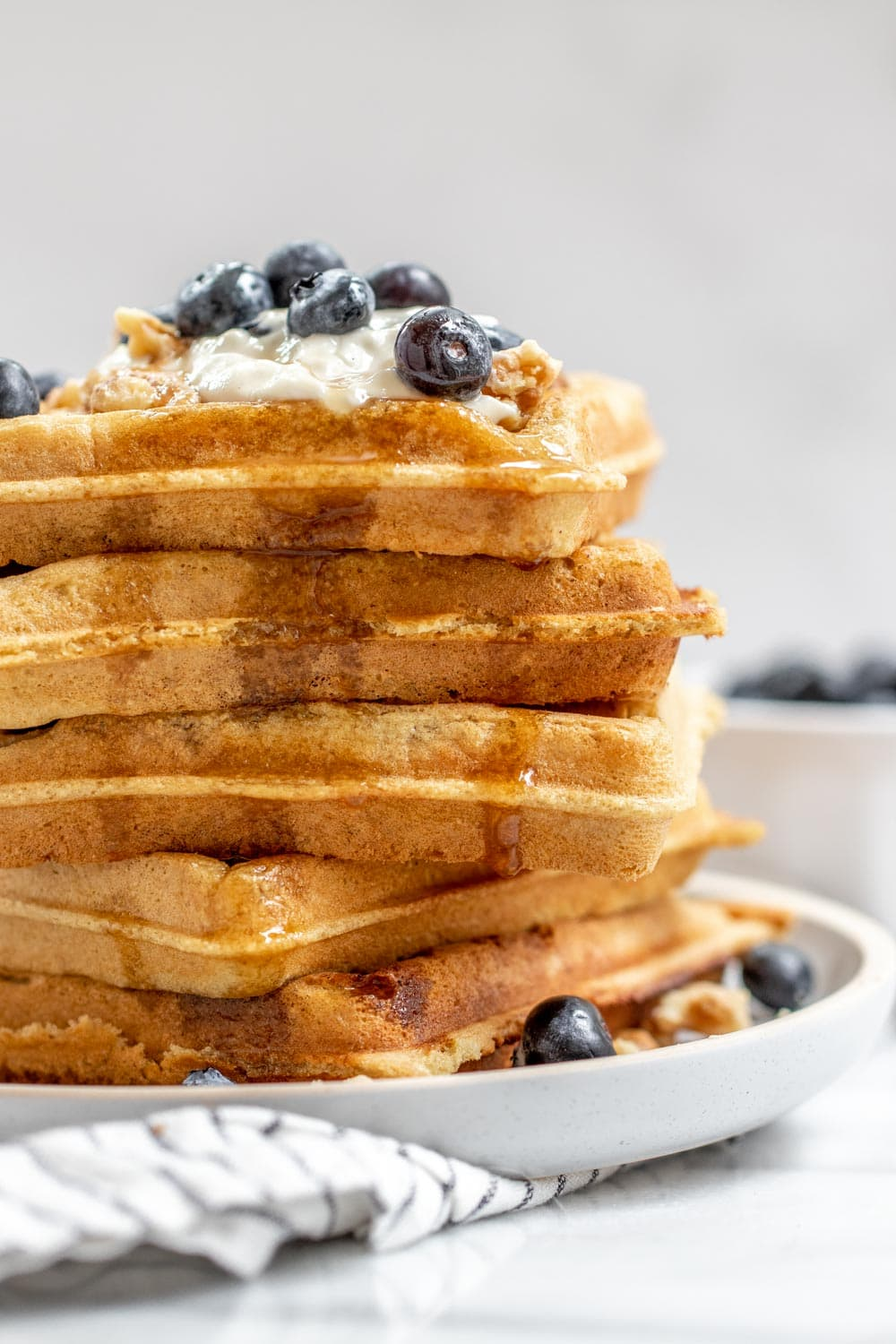Tall stack of vegan almond flour waffles with berries on top.