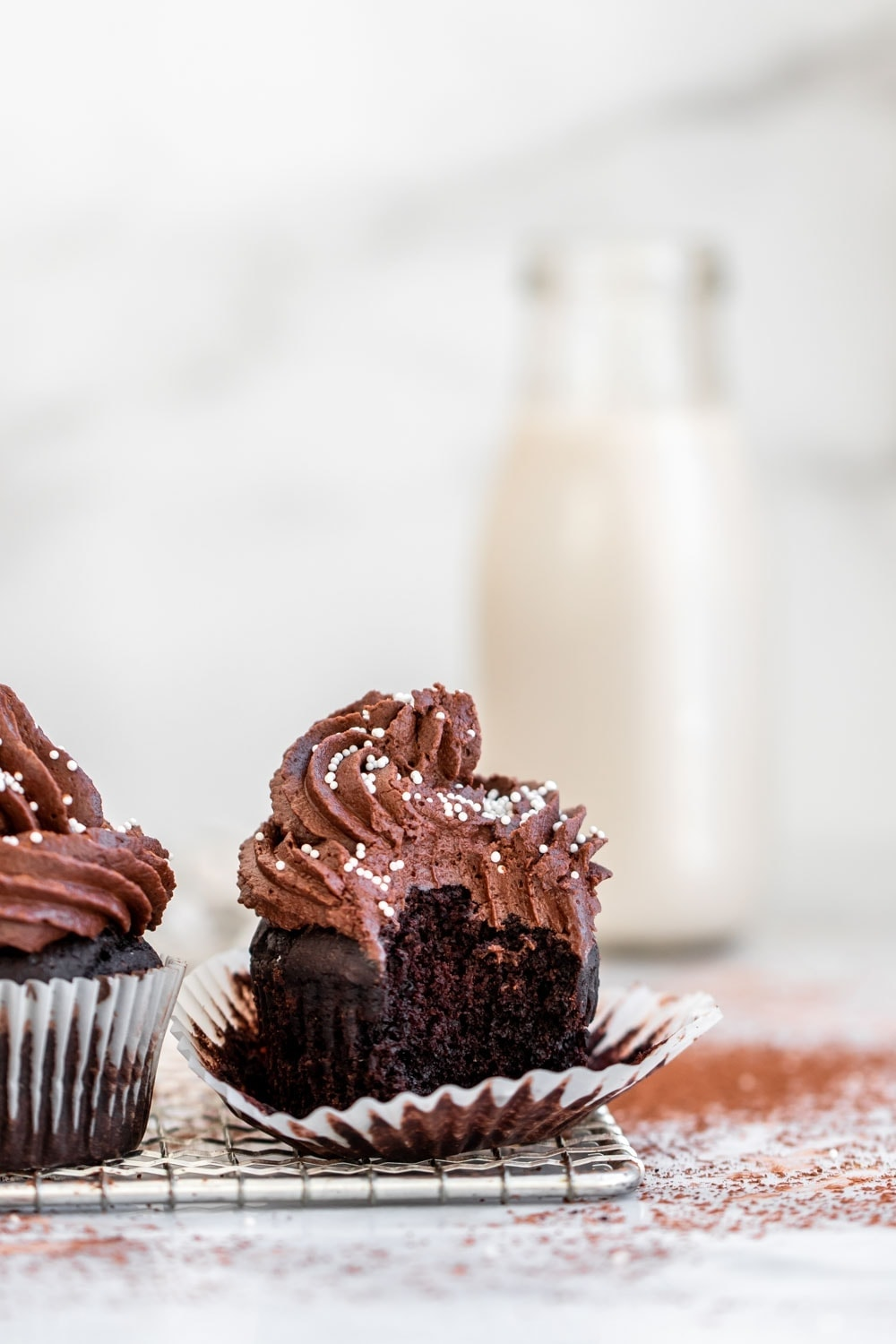 Gluten free chocolate cupcakes with a bite taken out.