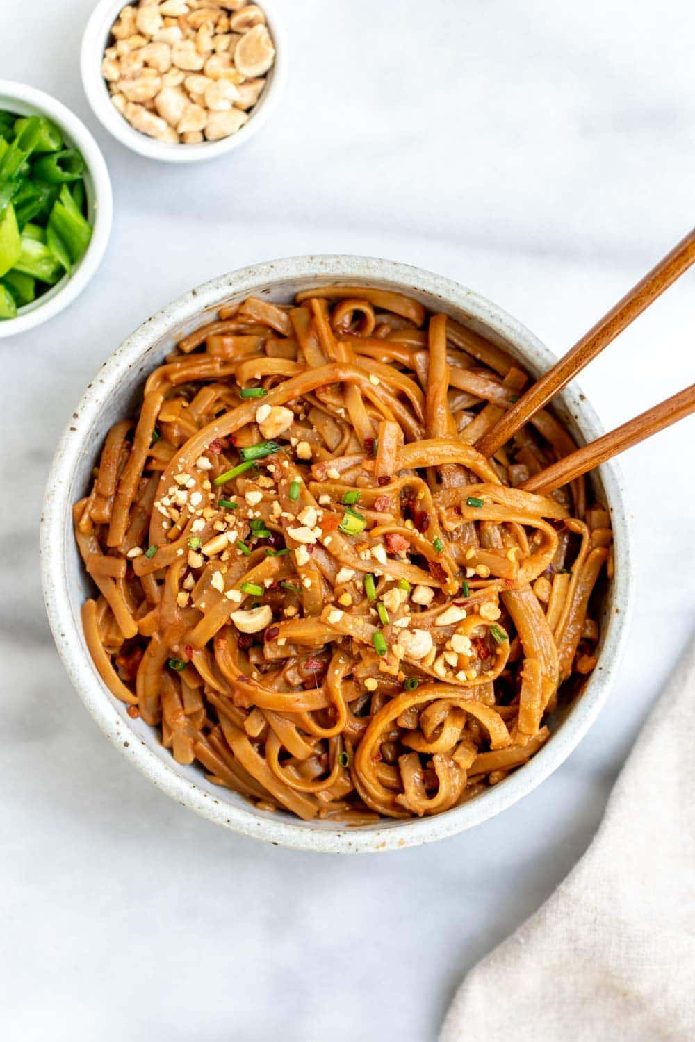 Bowl with spicy peanut butter noodles and chopsticks.