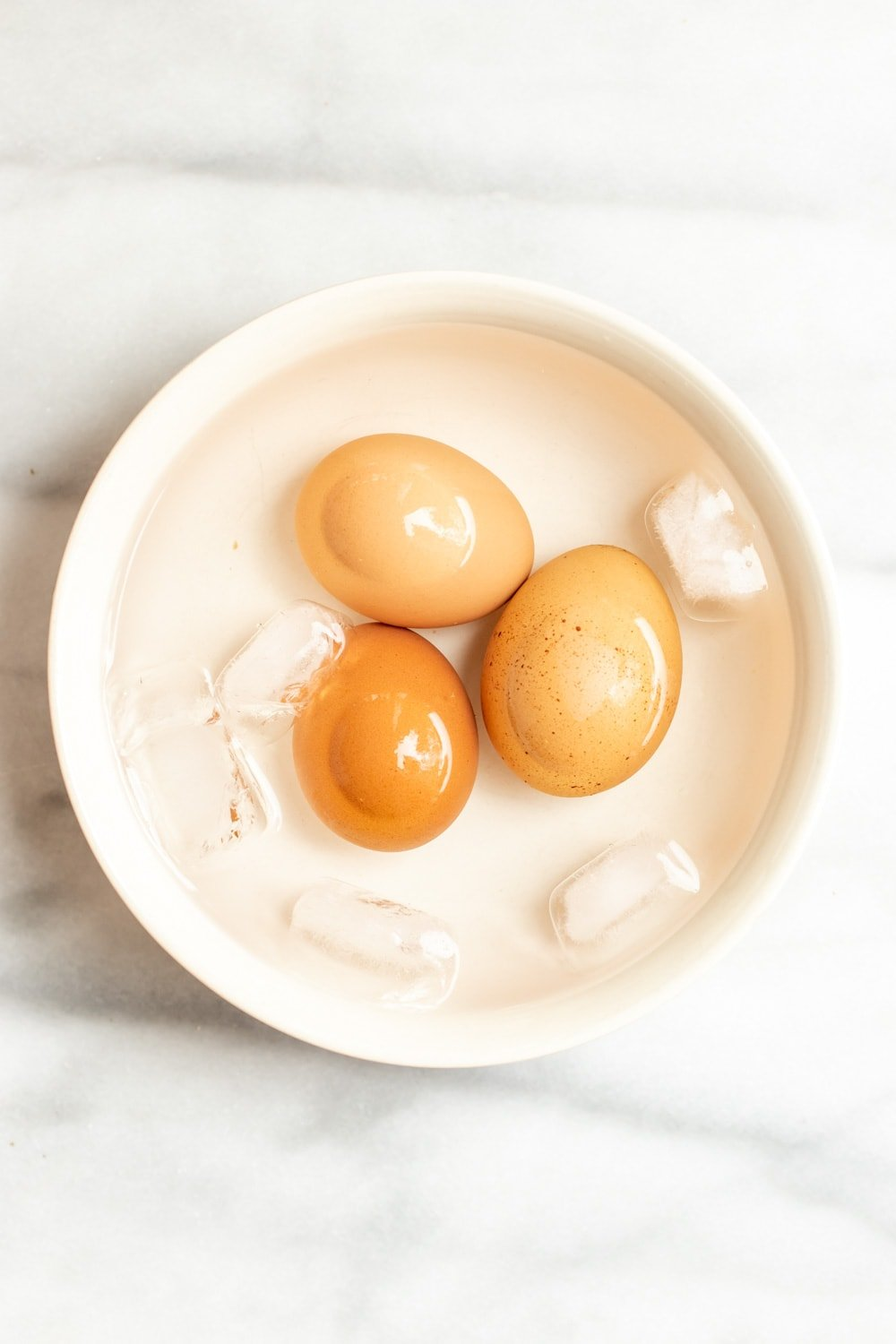 Three eggs in a bowl of ice water.