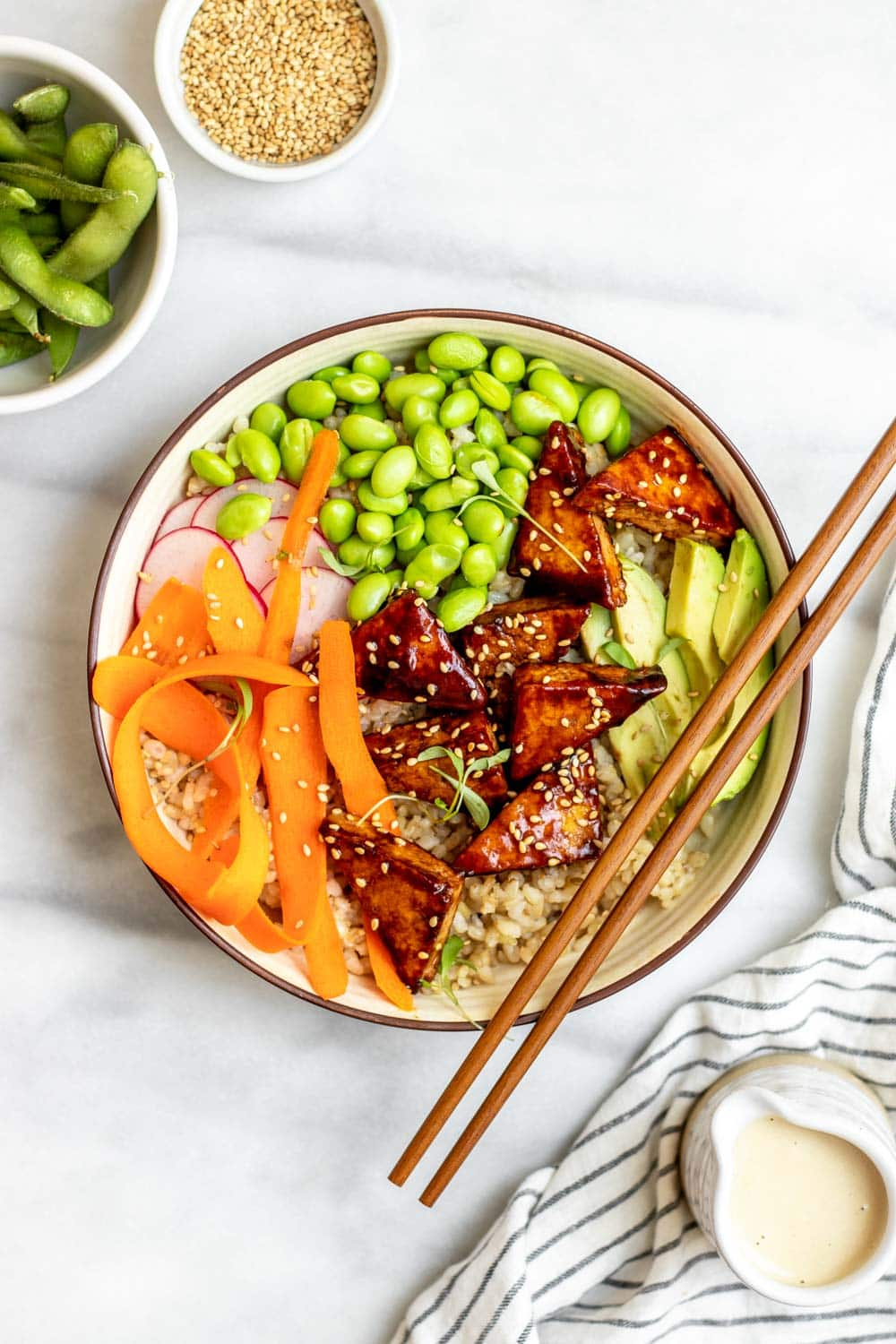 Overhead shot of vegan sushi bowl with chopsticks on the side.