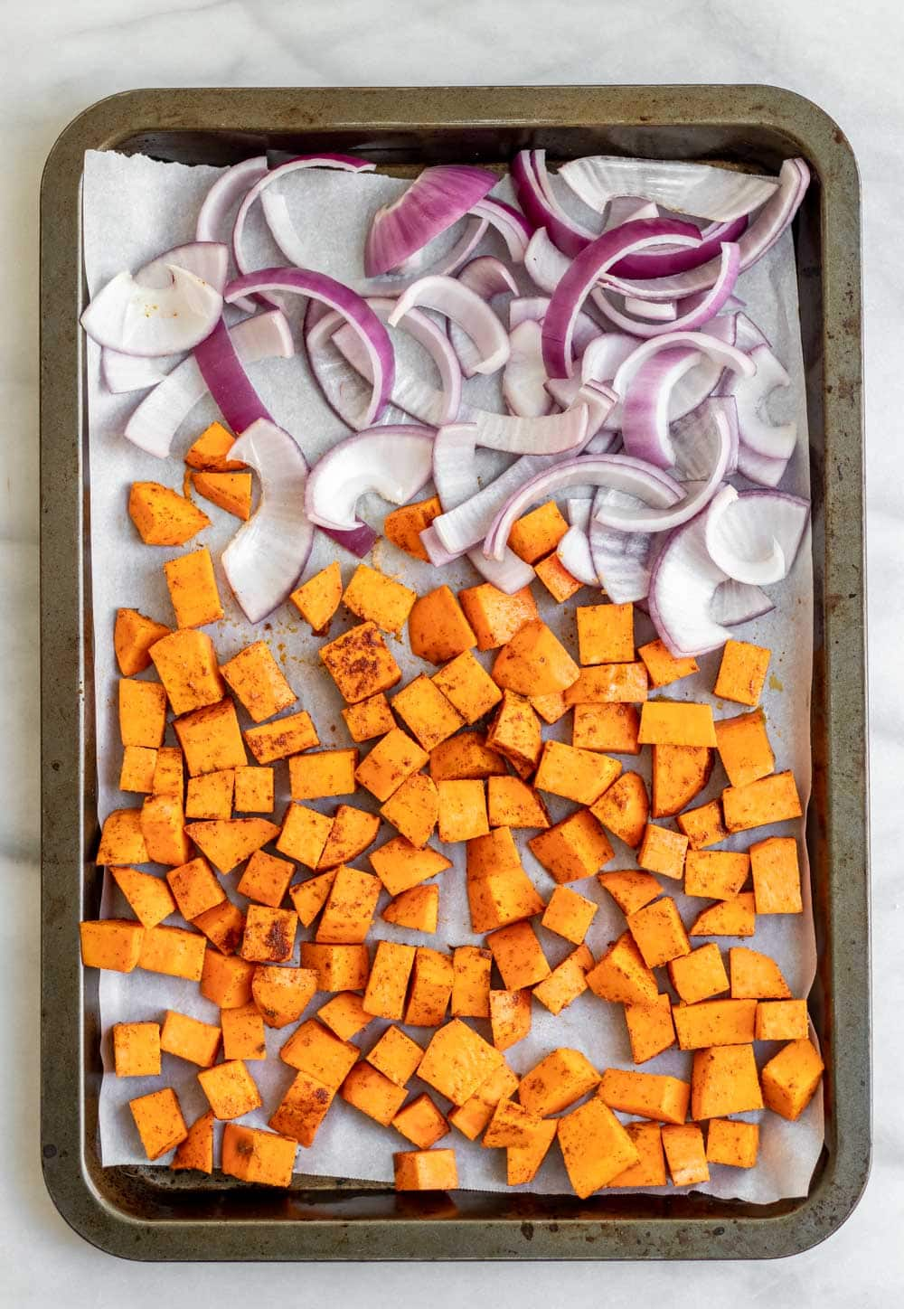 Cubed sweet potato and red onion on a baking tray.