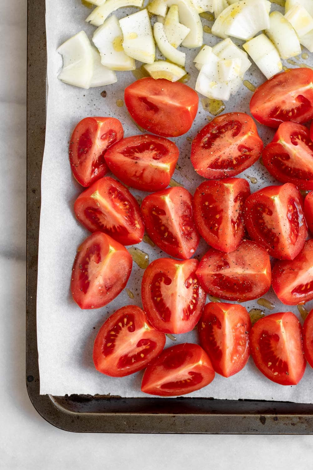 Fresh tomatoes chopped on a baking sheet.