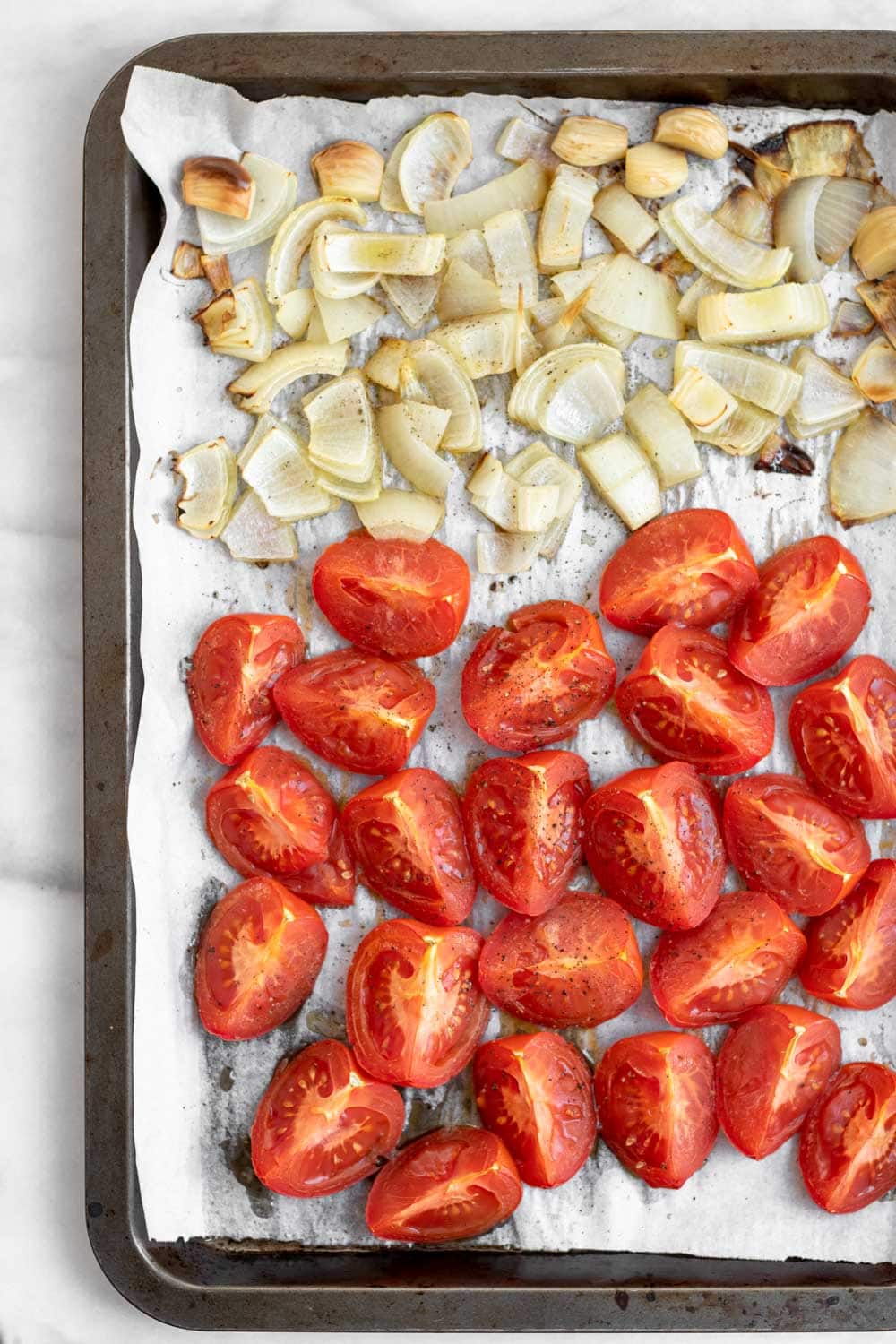 Roasted tomatoes and onion on a baking sheet.