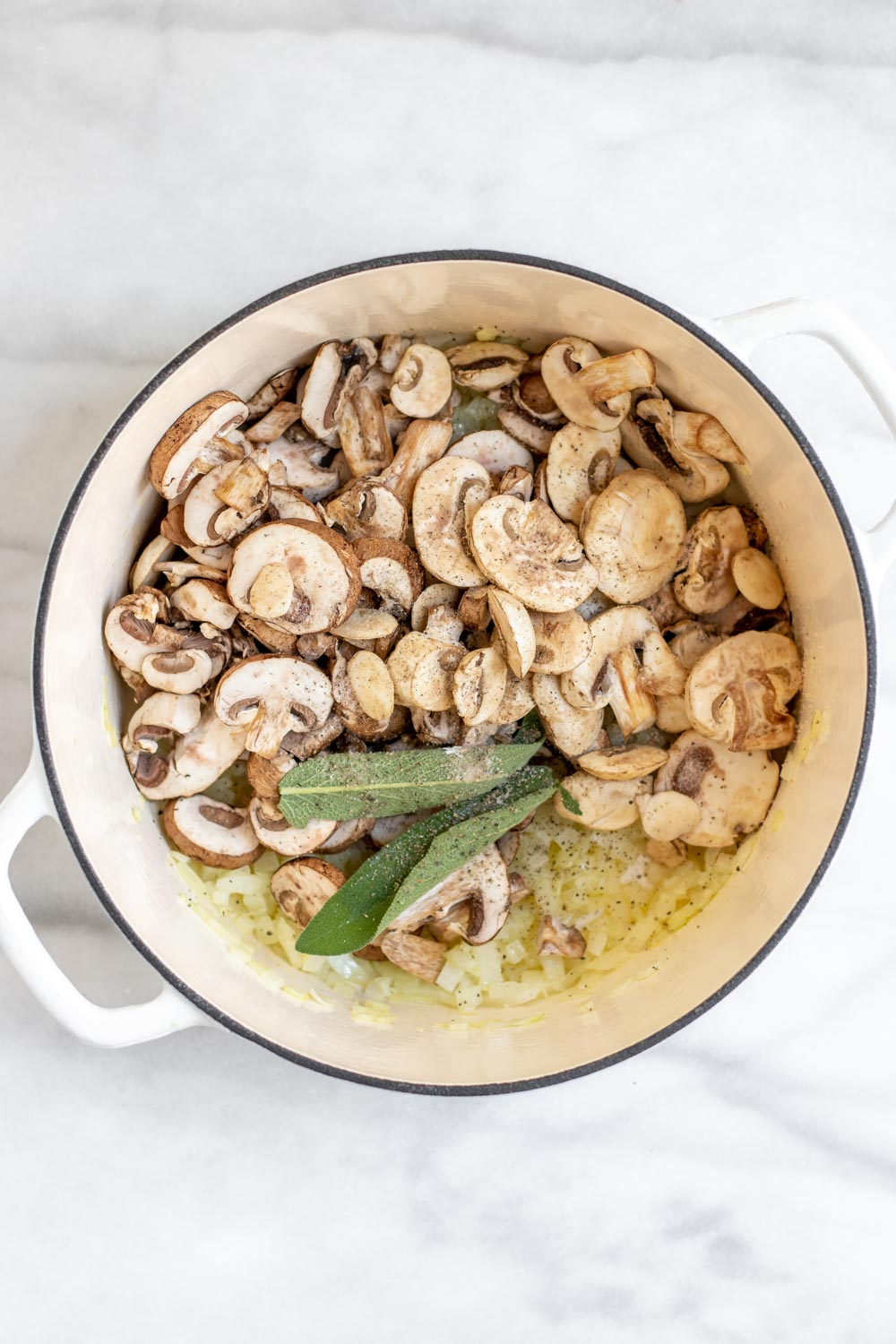 Mushrooms in a pot with sage and onions.