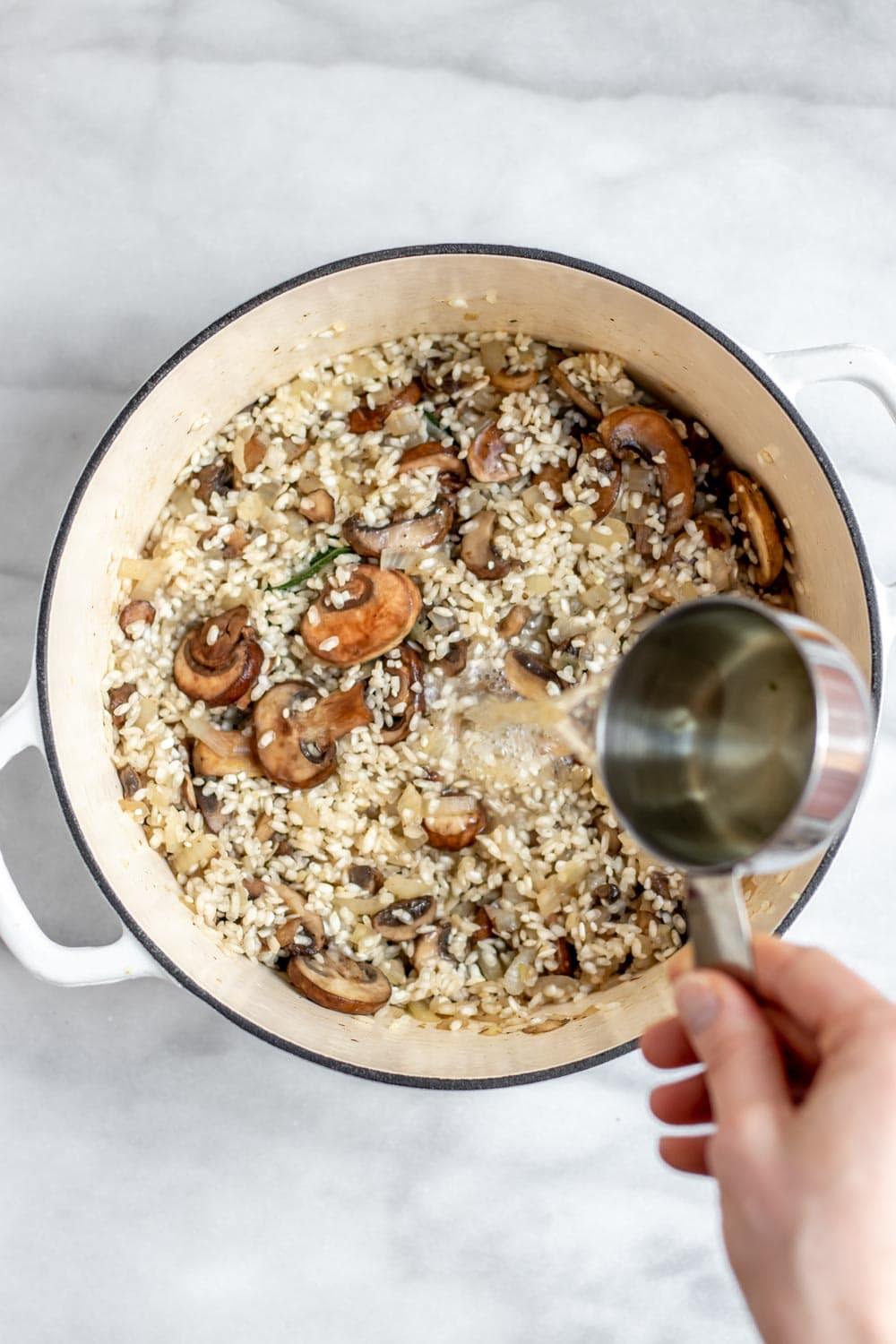 Pouring white wine into the pot with the risotto.