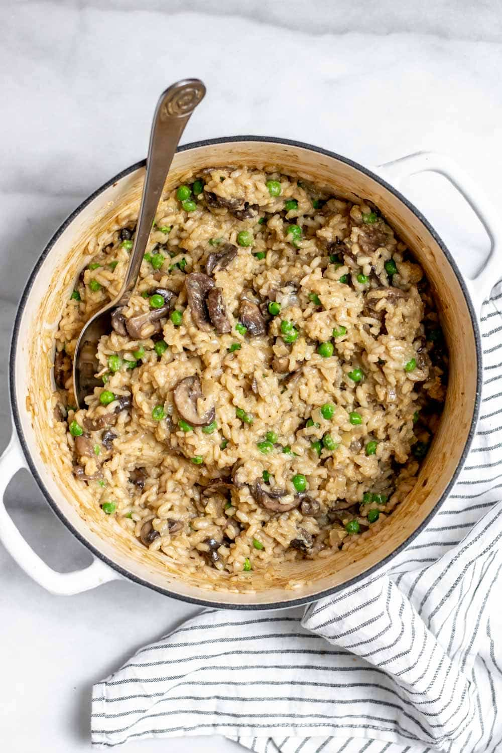 Large pot with vegan mushroom risotto with a spoon on the side.