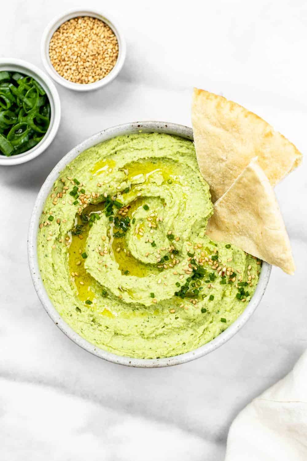 Edamame hummus in a small bowl with pita bread on the side.