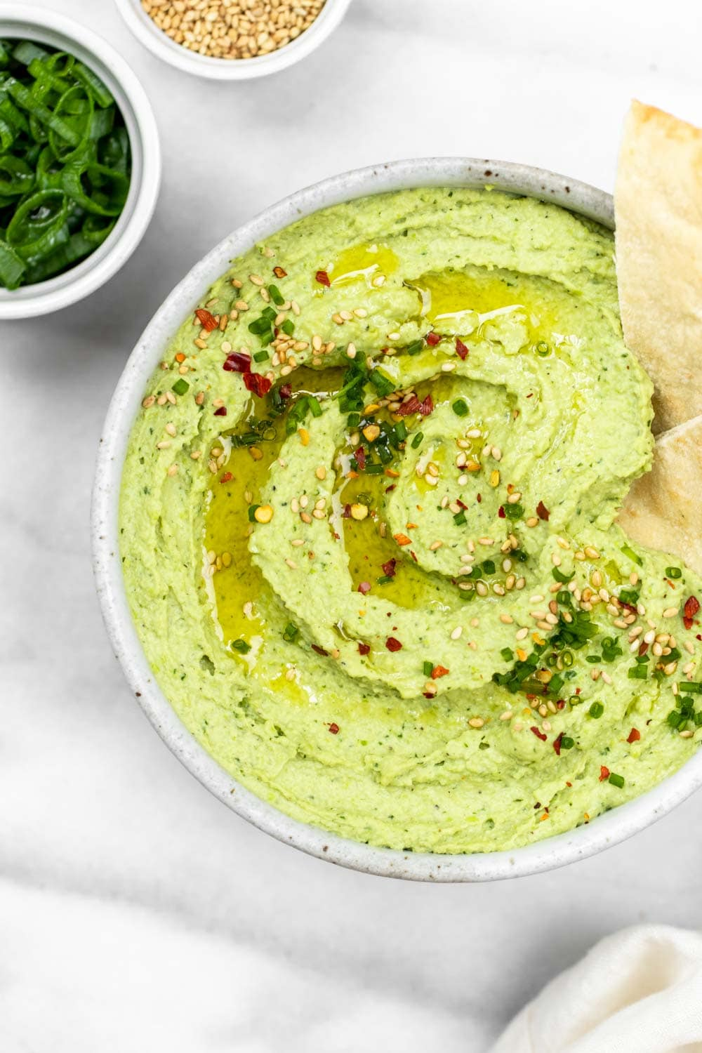 Close up image of the avocado and edamame hummus with sesame seeds on top.
