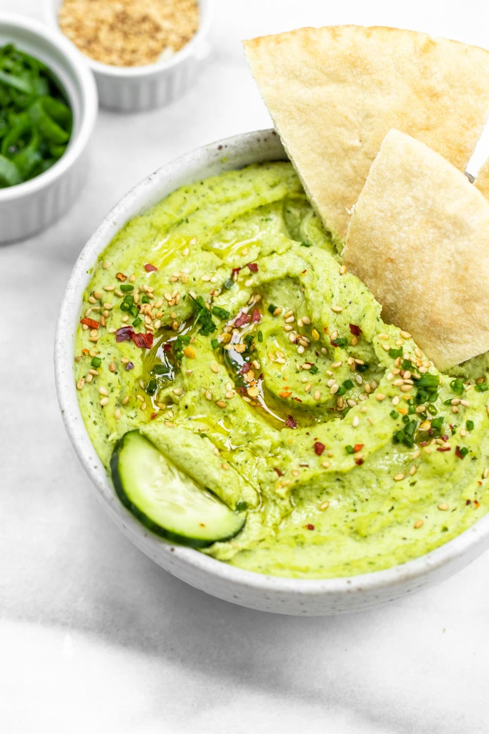 Angled view on the hummus with cucumber and pita in the bowl.