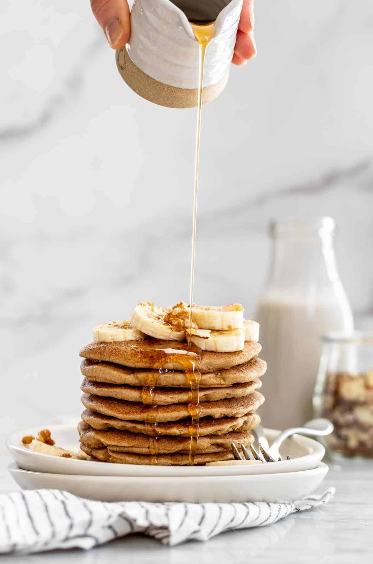 Pouring maple syrup on top of pancakes.