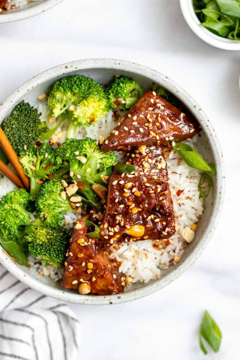 Vegan tempeh recipe with broccoli and rice in a small bowl.