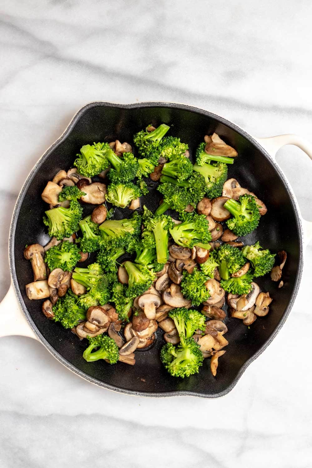 Mushrooms and broccoli sauteing in a pan.
