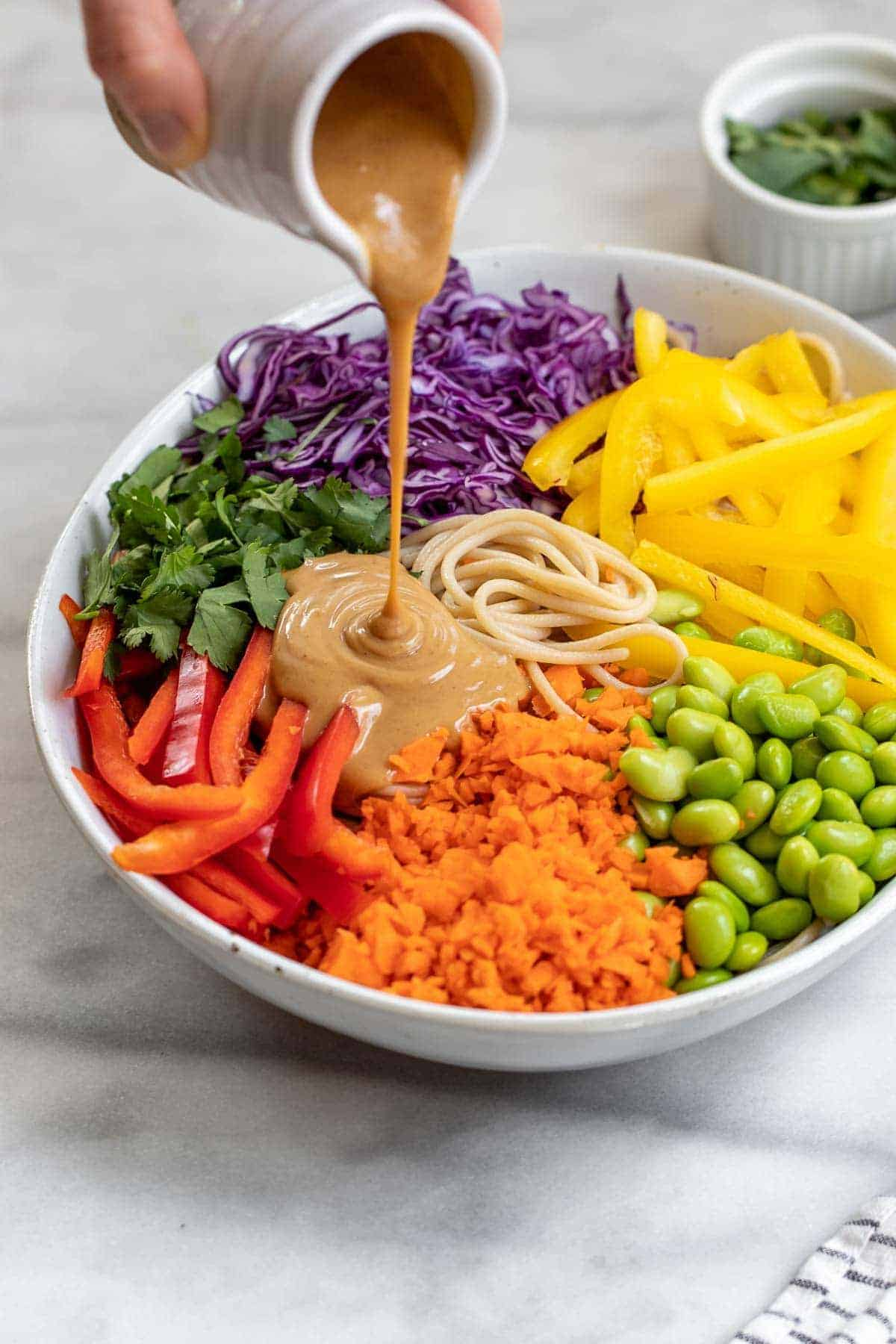 Pouring the thai peanut sauce over the noodles and veggies.
