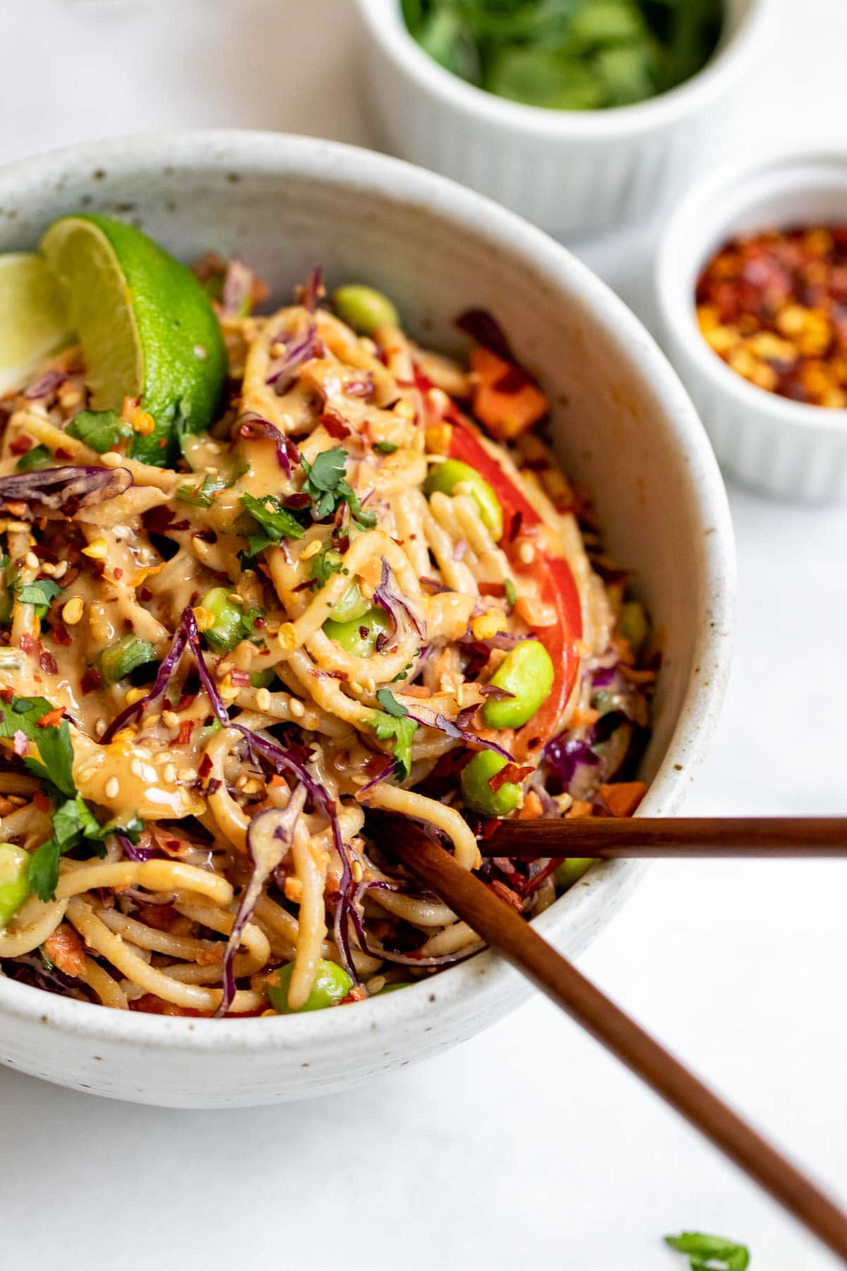 Small speckled bowl with peanut noodle salad with lime wedges.