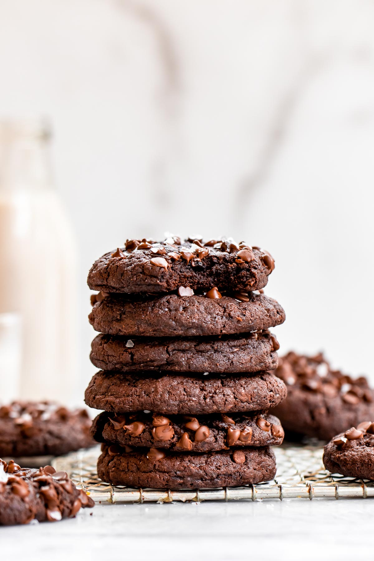 Six vegan chocolate cookies stacked on top of each other with milk in the background.