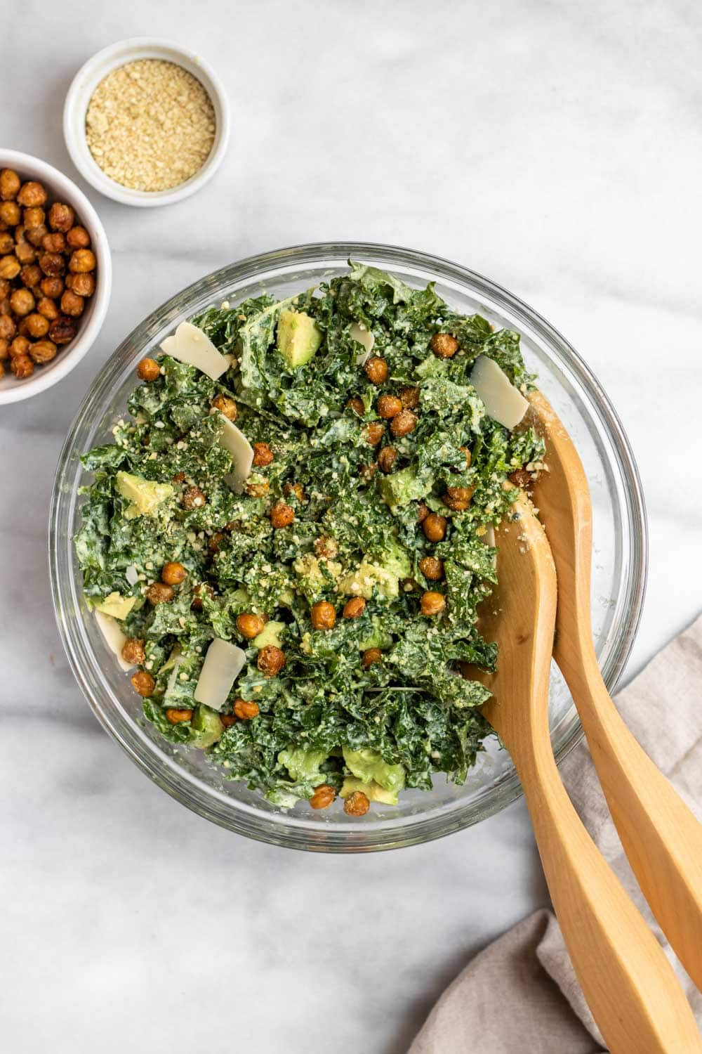 Large glass bowl with kale caesar salad, parmesan and crispy chickpeas on top.